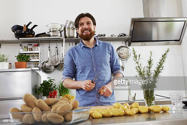 Smiling man preparing potatoes in kitchen