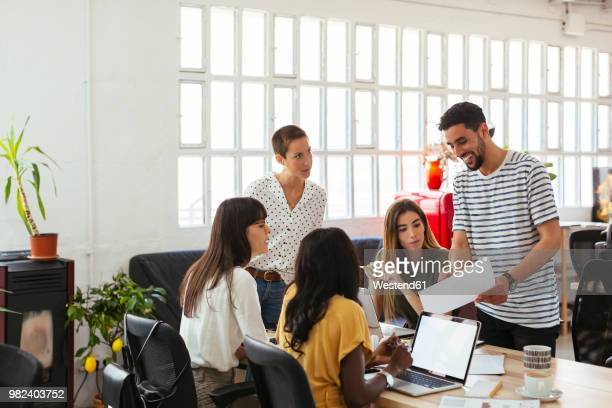 Smiling man presenting paper to colleagues at desk in office