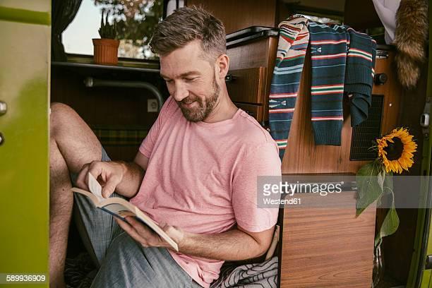 Smiling man reading a book in van