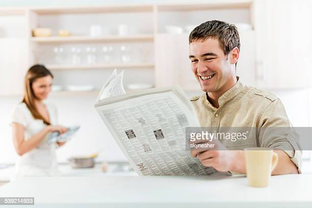 Smiling man reading newspapers.