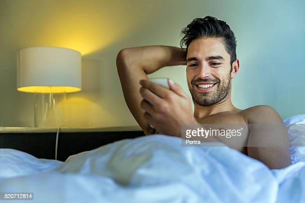 Lächelnder Mann liest SMS auf Handy