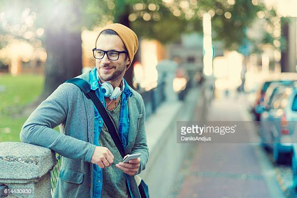 smiling man relaxing after work playing with his phone