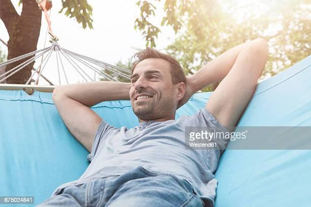 Smiling man relaxing in hammock