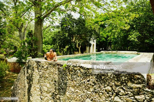 Smiling man relaxing on edge of pool at luxury tropical spa