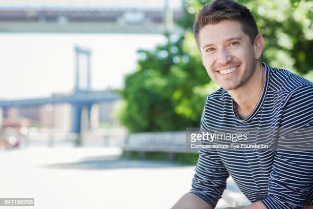 Smiling man relaxing on riverside by Manhattan Bridge, New York