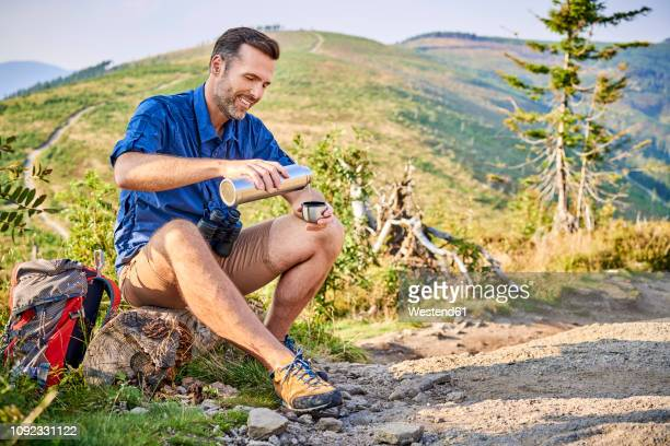 smiling man resting during hiking trip pouring cold water from thermos flask - calção - fotografias e filmes do acervo