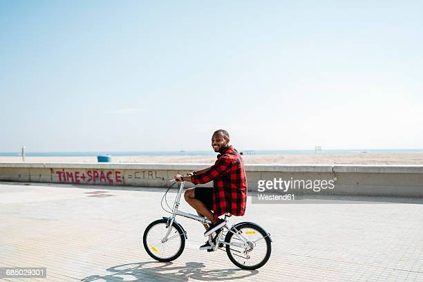 Smiling man riding bicycle near beach