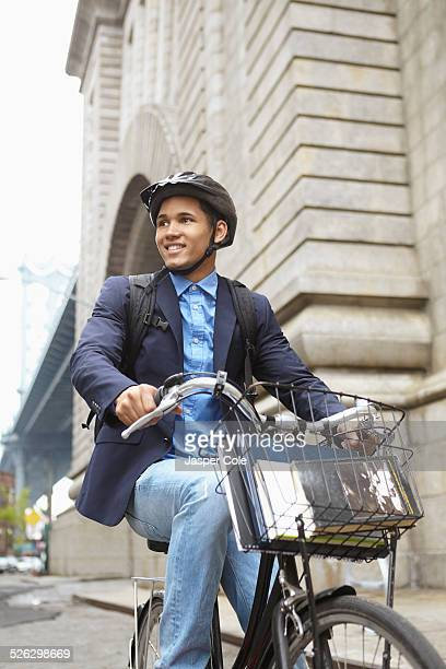 Smiling man riding bicycle on city street
