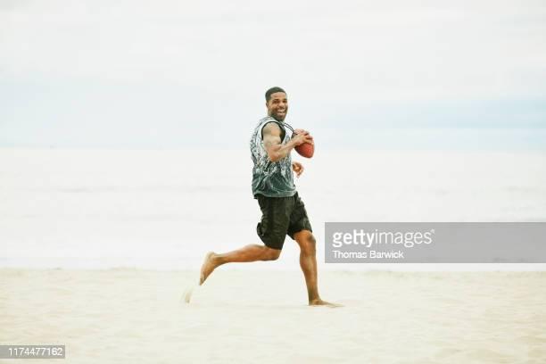 smiling man scoring touchdown during beach football game - barefoot black men stock pictures, royalty-free photos & images