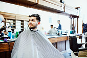 smiling man seated barbers chair waiting