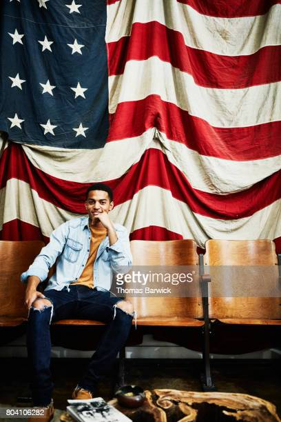 Smiling man seated in front of American flag