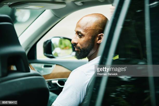 smiling man seated passenger seat car