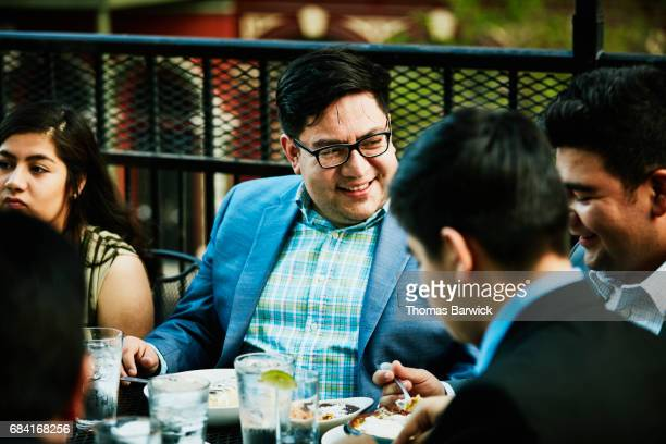 Smiling man sharing celebration meal with family on restaurant deck