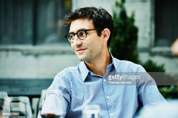 smiling man sharing dinner with friends on restaurant patio - 35 39 jahre stock-fotos und bilder