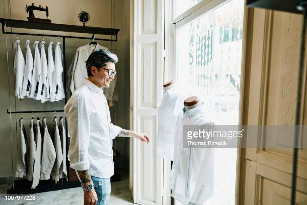 smiling man shopping in mens boutique - 白い服 ストックフォトと画像