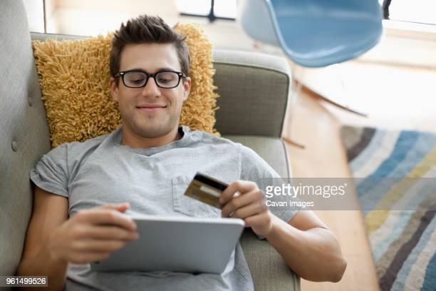 smiling man shopping online on tablet while lying on sofa at home - spending money stock pictures, royalty-free photos & images