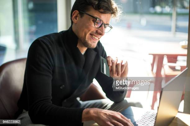 smiling man shopping. - making a reservation stock photos and pictures