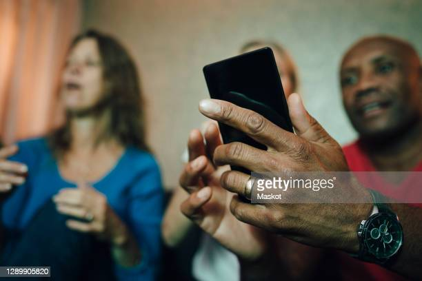 smiling man showing mobile phone to women during sporting event - fan enthusiast stock pictures, royalty-free photos & images