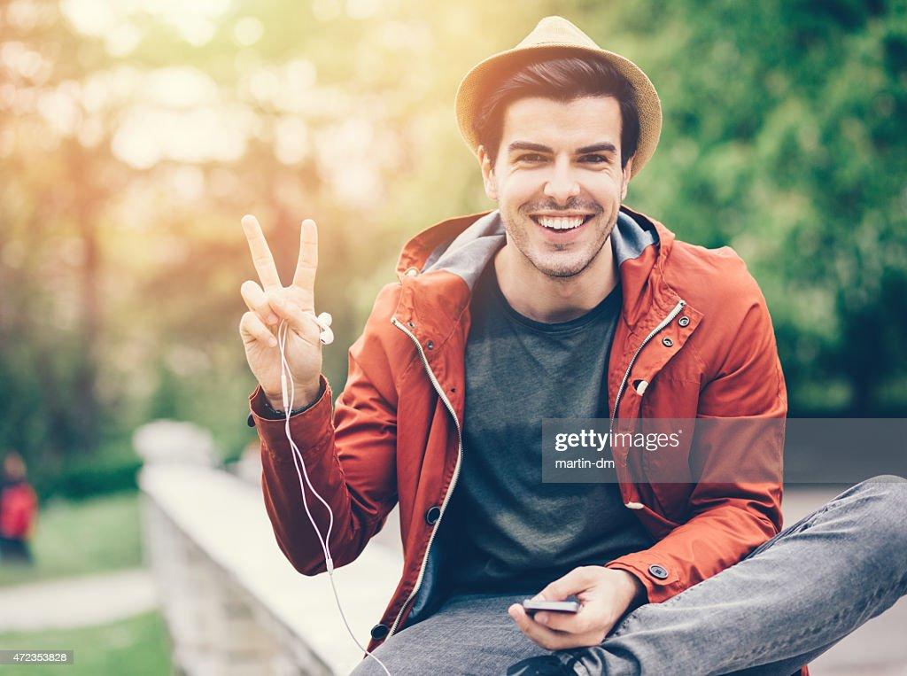 Lächelnder Mann zeigt das peace-Zeichen : Stock-Foto