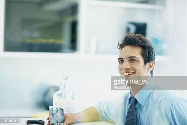 Lächelnder Mann sitzt in bar mit Glas whiskey
