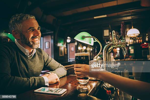 Smiling man sitting at counter of a pub