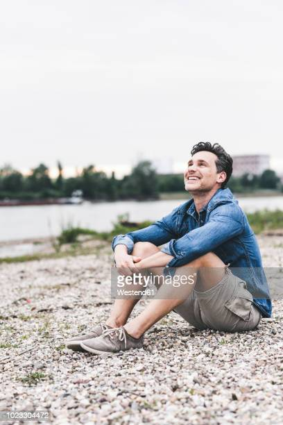 smiling man sitting at the riverside looking up - vertikal stock-fotos und bilder