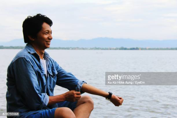 smiling man sitting by sea against sky - ko ko htike aung stock pictures, royalty-free photos & images