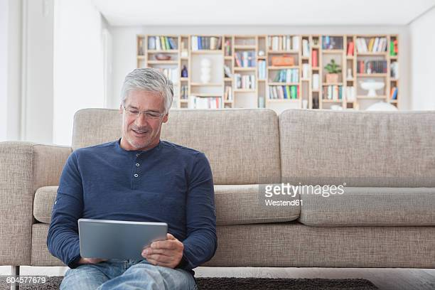 Smiling man sitting in front of the couch at home using digital tablet