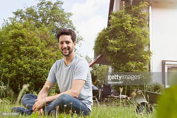 Smiling man sitting in garden