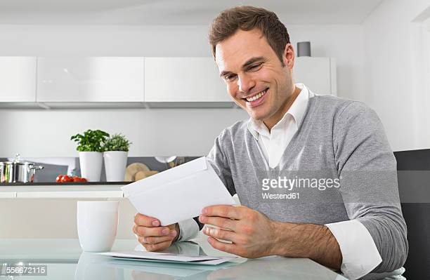 Smiling man sitting in kitchen watching envelope