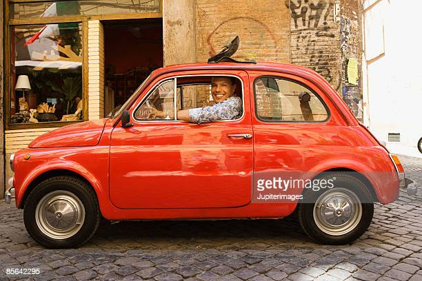 Smiling man sitting in sub-compact car