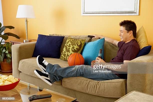 smiling man sitting next to basketball while watching television - man cave stock pictures, royalty-free photos & images