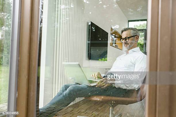 Smiling man sitting on chair in his living room using laptop