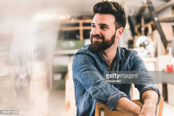 smiling man sitting on chair in workshop - drehen stock-fotos und bilder