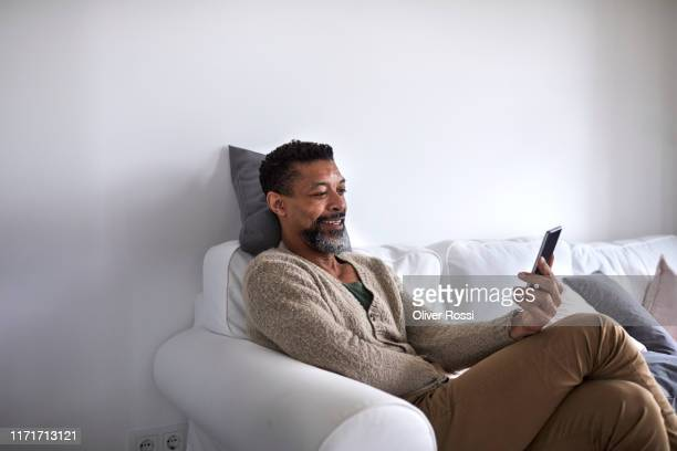 smiling man sitting on couch using cell phone - one man only stock pictures, royalty-free photos & images