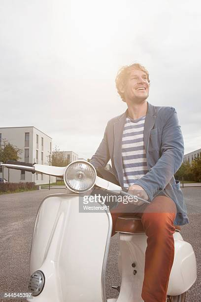 Smiling man sitting on his motor scooter at backlight