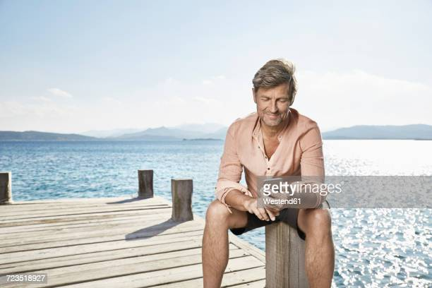 Smiling man sitting on jetty looking at cell phone