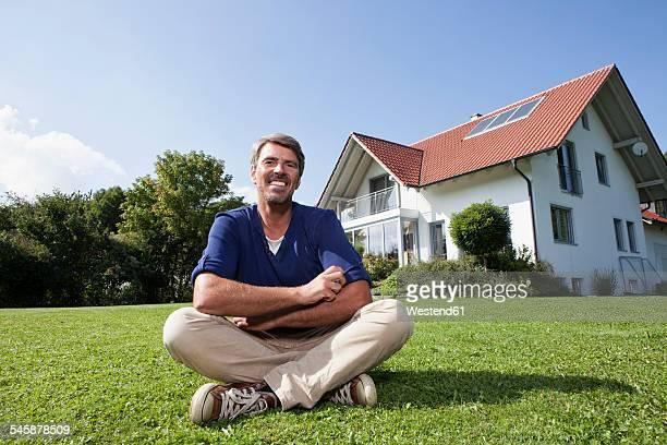 Smiling man sitting on lawn in garden