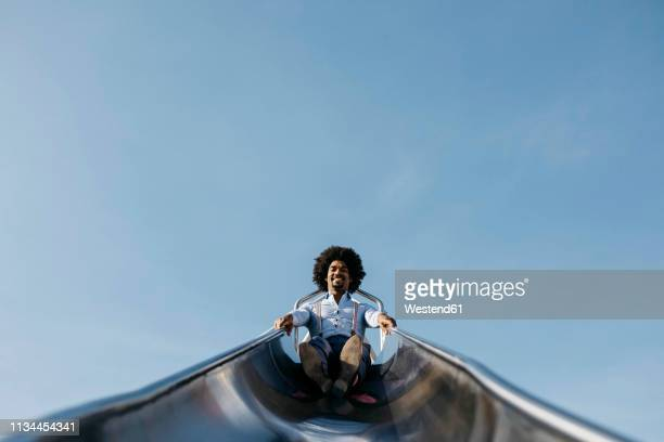 smiling man sitting on slide - sliding stock pictures, royalty-free photos & images