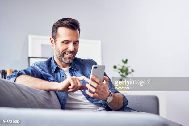 smiling man sitting on sofa using cell phone - homens imagens e fotografias de stock