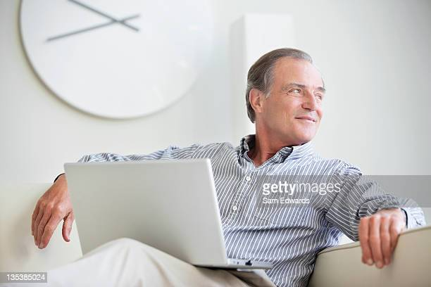 smiling man sitting on sofa with laptop - looking over shoulder stock pictures, royalty-free photos & images