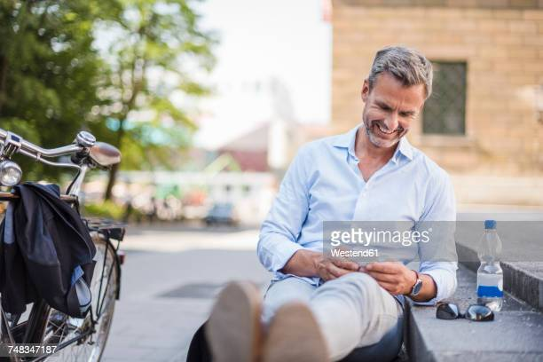 Smiling man sitting on stairs in the city using cell phone