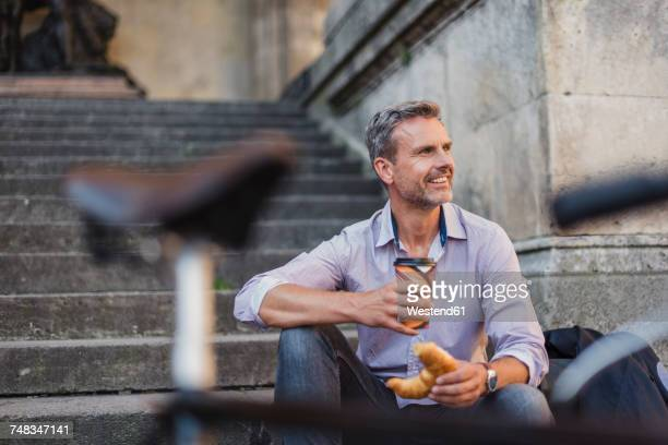 Smiling man sitting on stairs with croissant and takeaway coffee in the city