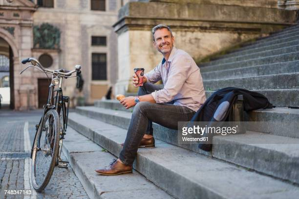 Smiling man sitting on stairs with takeaway coffee in the city
