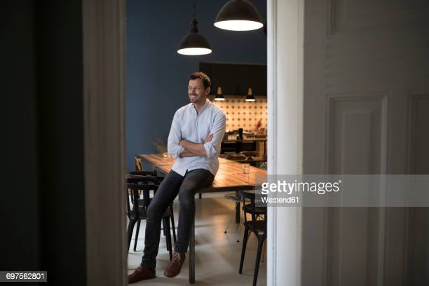 smiling man sitting on table in his kitchen - reichtum stock-fotos und bilder