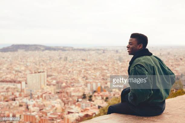 Smiling man sitting on terrace overlooking city