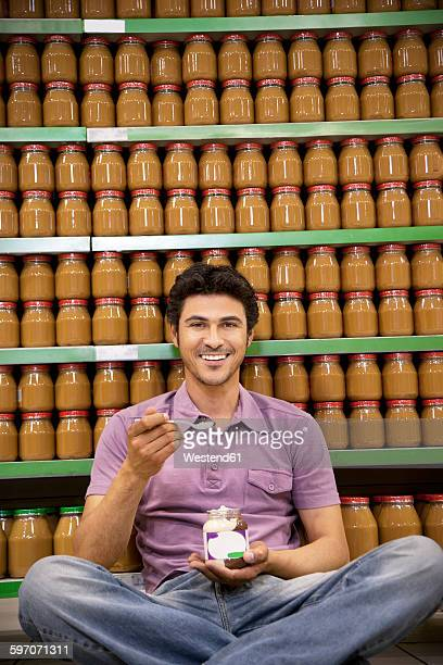 Smiling man sitting on the floor of a supermarket tasting glass of chocolate spread