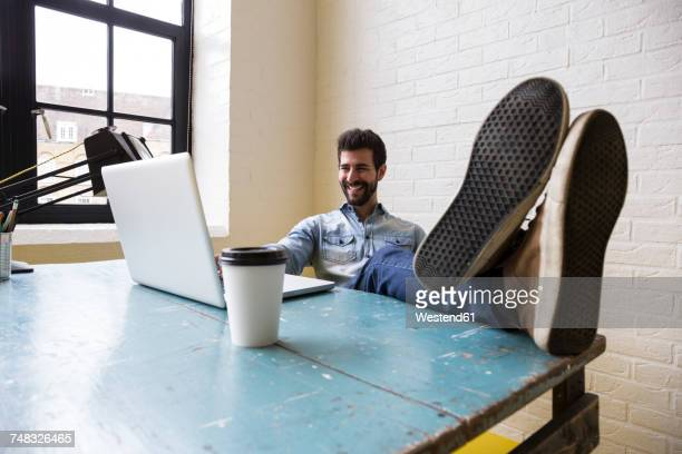 Smiling man sitting with feet up at desk looking at laptop