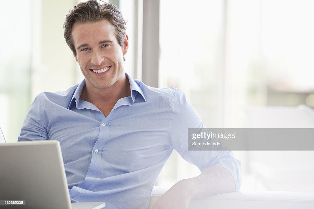 Smiling man sitting with laptop : Stock Photo