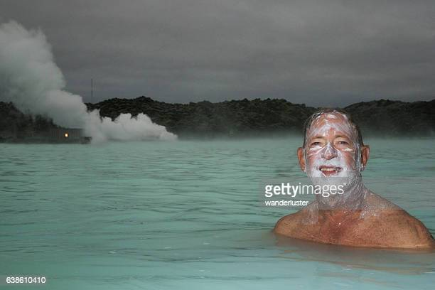 Smiling man soaking in hot springs